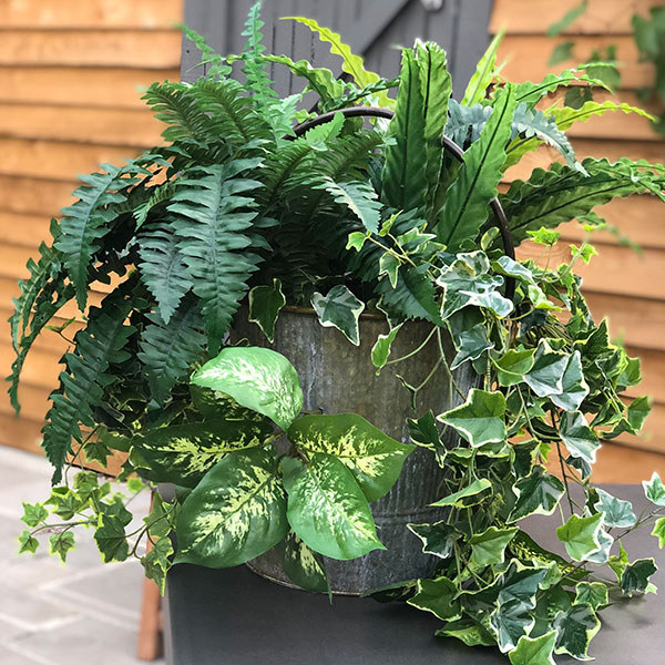 Hanging bucket filled with faux plants by Twilight Trees